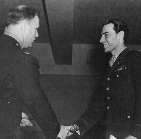 O capitão Oscar O'Neill recebendo uma condecoração e o texto que existe no verso desta foto