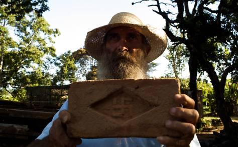 """José Ricardo Rosa, 55, conhecido como """"Tatão"""" segurando um tijolo com a suástica nazista; após herdar a fazenda Cruzeiro do Sul na cidade de Campina do Monte Alegre ele encontrou por acaso tijolos com o sinal nazista usados na construção -"""