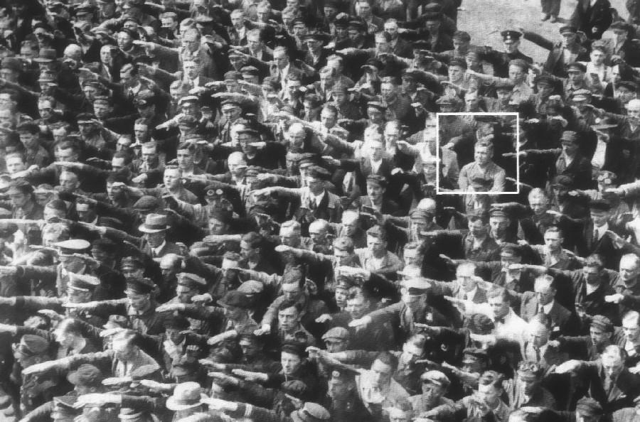 No destaque vemos  August Landmesser sem realizar a saudação nazista, em uma solenidade onde o próprio Hitler estava presente