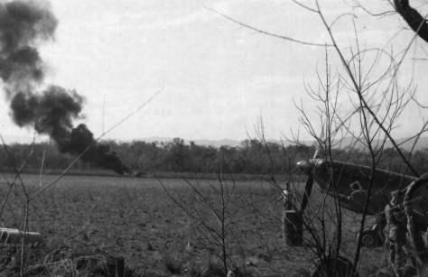 Em um campo de pouso vemos no primeiro plano o nariz de um Spitfire e ao fundo um caça japonês abatido e queimando.