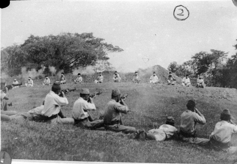 Soldados japoneses atirando em prisioneiros indiano da etnia Sikh, que estão sentados com os olhos vendados em um semi-círculo a cerca de 20 metros de distância. Fotografia encontrada entre os registros japoneses quando as tropas britânicas reocuparam Cingapura.