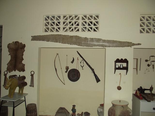 Artigos de caça. A arma de fogo de percurção é a famosa Lazarina, o arco é um Bodoque. Já a pele na extrema esquerda da foto é de um gato maracajá e a longa pele estirada na parede, com 2,73 metros, é de uma jiboia morta no Sítio Alegre, zona rural de Cuité, na década de 1940.