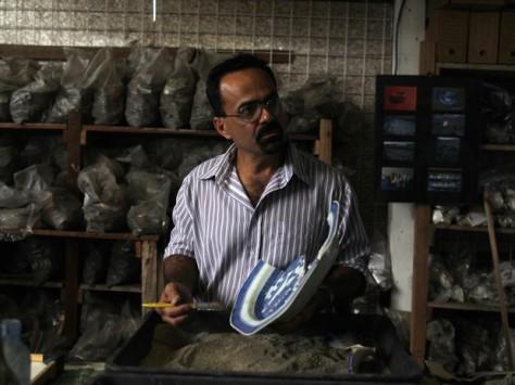 Arqueólogo Claudio Prado de Mello limpa peça de cerâmica encontrada durante obras de expansão do Metrô do Rio (Foto: Pilar Olivares/Reuters)