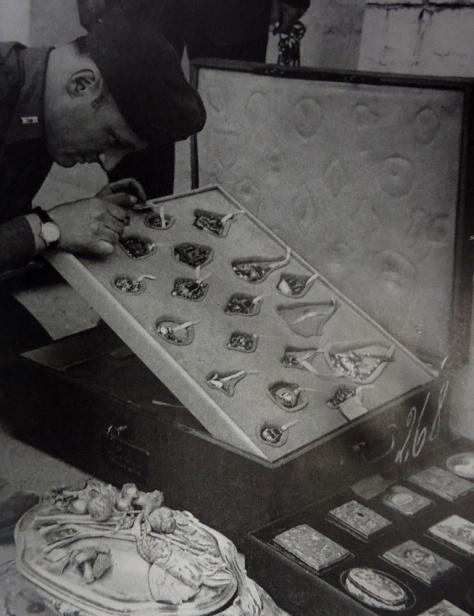 O tenente James R. Rorimer, na vida civil um curador de arte medieval do Metropolitan Museum of Art, de Nova York, examina uma coleção de joias italianas do século XVI, da coleção Rothschild