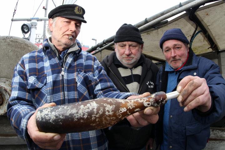 Konrad Fischer, Klaus Matthiesen e Thomas Buick seguram a mensagem da antiga garrafa no barco de pesca Maria I, em Kiel, Alemanha.