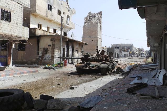 Abandoned tank is seen on a street near the damaged minaret of the Omari mosque in Deraa