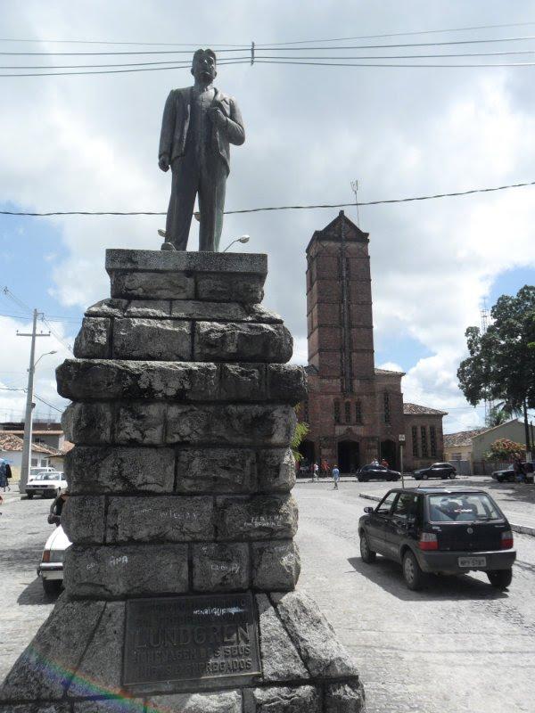 Estátua de João Ftrederico Lundgren, fundador da Companhia de Tecidos Rio Tinto, no cetro da cidade paraibana de Rio Tinto. Ao fundo a Igreja Matriz de Santa Rita de Cassia.