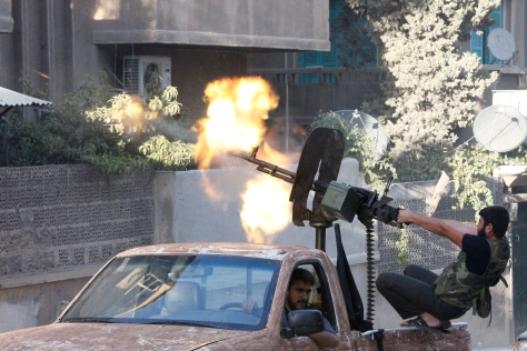 A MEMBER OF FREE SYRIAN ARMY OPEN FIRE FROM HIS MACHINE GUN DURING CLASHES WITH SYRIAN ARMY FORCES IN ALEPPO