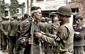 - O tenente Paul Unger, da polícia do exército americano, lotado na segunda divisão blindada, revista o prisioneiro Kurt Peters, um membro da SS, com a patente de Untersturmführer (equivalente a segundo-tenente), que pertencia ao III. Battalion, do SS-Panzergrenadier Regiment 37, parte integrante da 17. SS-Panzergrenadier, a conhecida Division Götz von Berlichingen. Foto realizada na área de Notre-Dame-de-Cenilly, 18 quilômetros a sudoeste da cidade de Saint Lô, França, no dia 27 de julho de 1944.