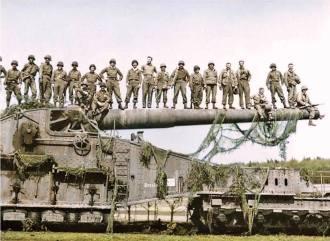 - Soldados norte-americanos da 10th Armoured e da 45th Division, ambos do 7th Us Army, posam sobre um potente canhão ferroviário alemão em Rentwertshausen, Alemanha. Abril de 1945.