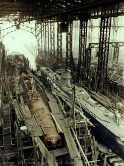 """- Submarinos alemães tipo VII-C durante a construção nos estaleiro da empresa Blohm und Voss, em Hamburgo, 1940. Os dois submarinos aqui retratados são do mesmo tipo, o da esquerda está mostrando o casco de pressão """"interior"""". A construção de submarinos alemães nunca conseguiu suprir as necessidades para deter o fluxo de homens e armas Aliadas que atravessavam principalmente o Oceano Atlântico. Como resultado, a campanha para cortar as linhas de comunicação marítimas aliadas falhou. Colorizado por Edward Tambunan, da Indonésia."""