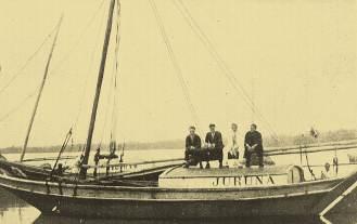 """Barca paraense """"Juruna"""", vendo sentados, da esquerda para direita, Duggan, Olivero, Mestre Josino Campos (comandante do barco) e Campanelli, no porto de Belém em 1926."""