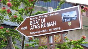 """Há sinais que avisam """"Kapal rumah di atas"""", que significa """"o navio em cima da casa"""" e uma placa dá detalhes de como a arca improvisado salvou 59 pessoas."""
