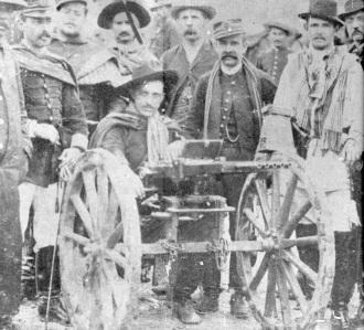 Coronel Dulcídio (militar com menor estatura) em pé, atrás de uma metralhadora Nordenfelt - Fonte - Wikipédia