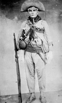 Um membro das forças de repressão contra o cangaço em 1927. Apesar da roupa ser muito próxima aos cangaceiros, a indumentária dos componentes da repressão era normalmente mais simples em termos de adornos.