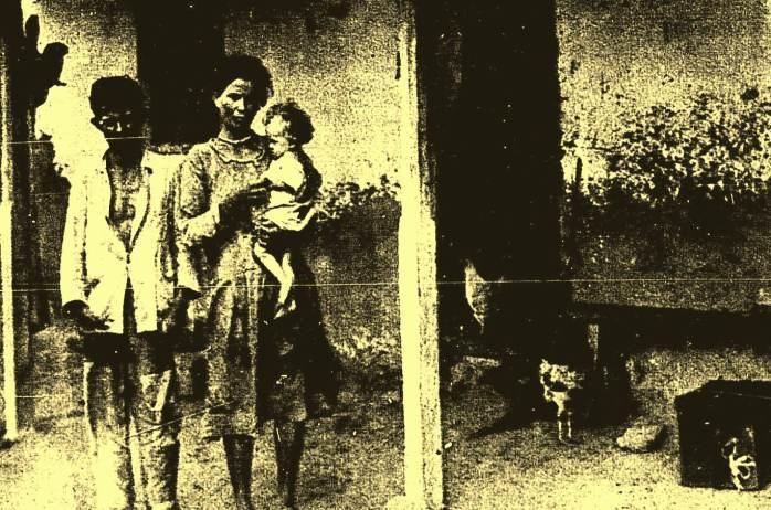 Joaquim Gomes Cardoso, sua esposa e filho diante de sua casa no lugar Passagem.