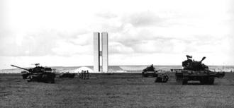 Tanques em frente ao Congresso Nacional patrulham a Esplanada dos Ministérios, em Brasília, após o golpe militar de 1964 - Fonte - https://pt.m.wikipedia.org/wiki/Ditadura_militar_no_Brasil_(1964-1985)