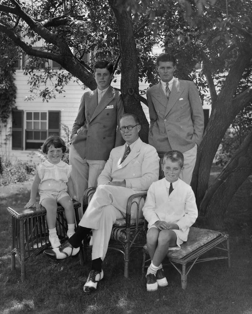 Young-JFK-with-double-breasted-combination-collar-pin-with-father-Joe-and-siblings